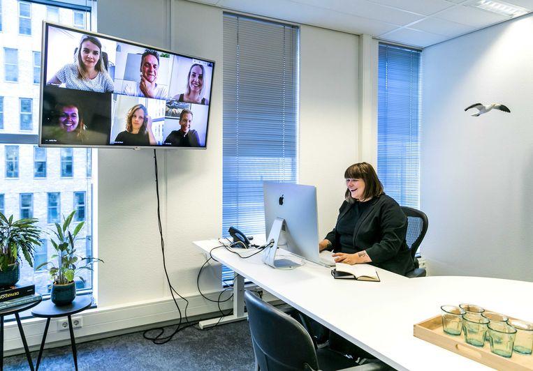 Een werknemer tijdens een videogesprek op kantoor. Online samenkomsten zijn geen goede vervanger van de offline variant, zo ervaren veel mensen. Beeld ANP