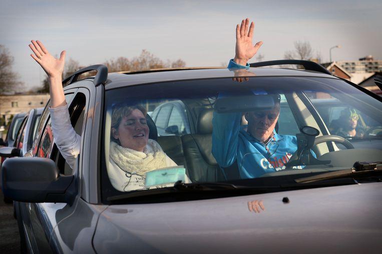 Kerkgangers volgen via hun autoradio een drive-in-kerkdienst van de Evangelische Gemeente op het parkeerterrein van de Veenendaalhal. Beeld null