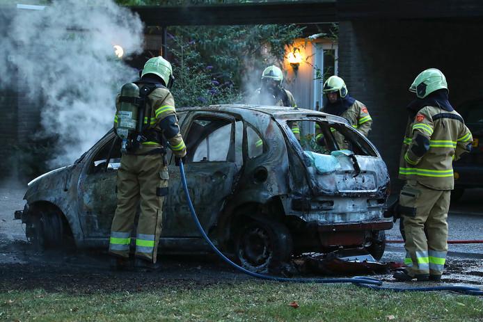 De brandweer bij de volledige uitgebrande auto.