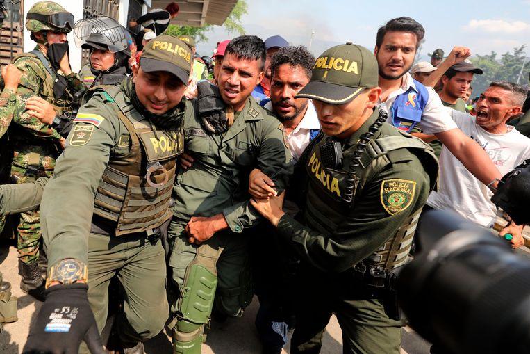 Colombiaanse politieagenten begeleiden in Cúcuta een overgelopen Venezolaanse soldaat. Beeld AP