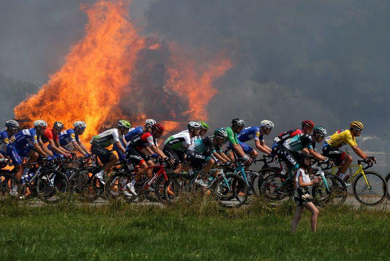 Het peloton passeerde voorbij brandende hooibalen.