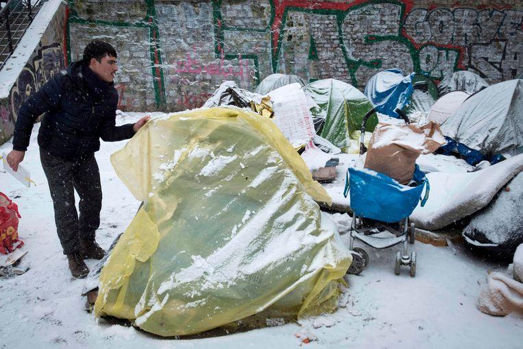 Een Afghaanse vluchteling bedekt bij vriestemperaturen zijn tentje met plastic in Parijs.