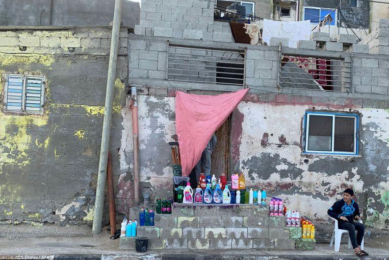 Een Palestijnse jongen verkoopt desinfecteermiddelen in Gaza.  Beeld Reuters