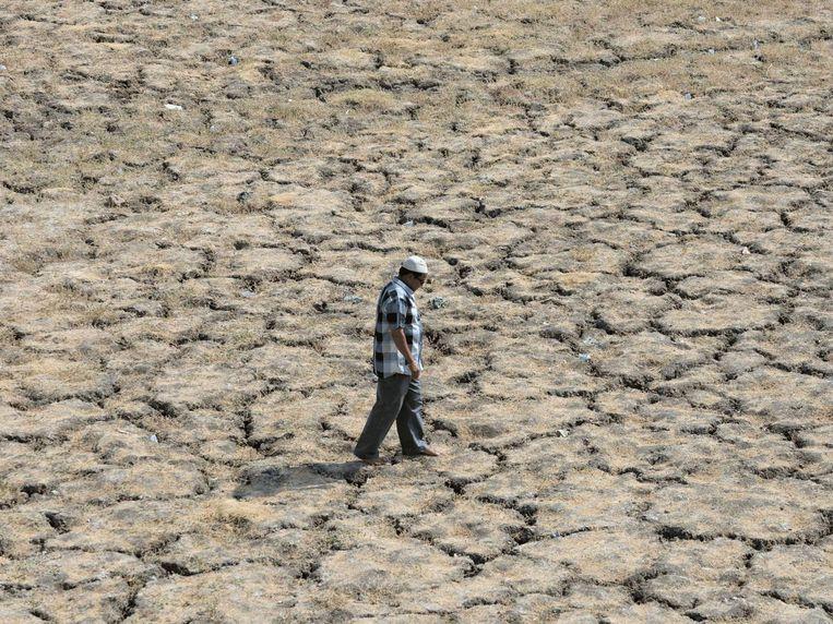 Een Indiase man wandelt op de uitgedroogde bedding van het meer Ahmad Sar in Ahmedabad, in de Indiase deelstaat Gujarat.
