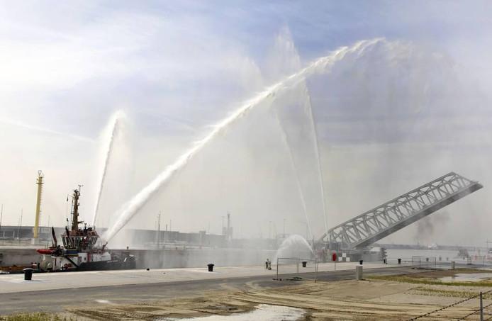 Onder eresaluut gaat de brug van de Kieldrechtsluis open voor het eerste schip. De sluis is de grootste ter wereld.