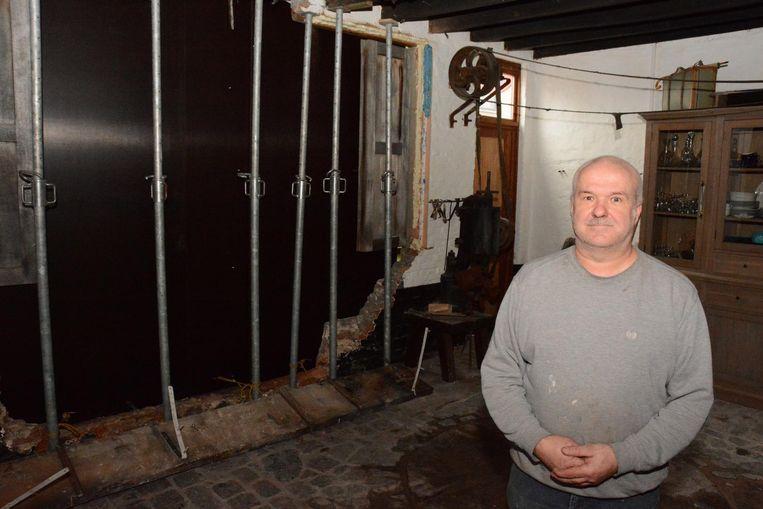 Bewoner Peter Heyrman bij de gestutte muur in de eetkamer.