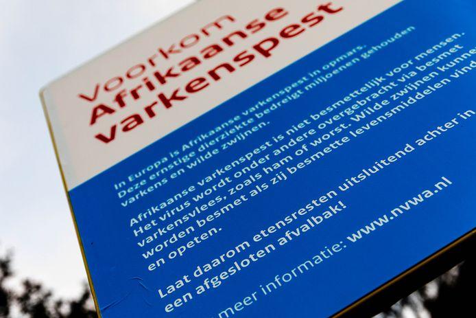 Een waarschuwingsbord van de NVWA tegen de verspreiding van Afrikaanse varkenspest op een parkeerplaats langs de snelweg A67.