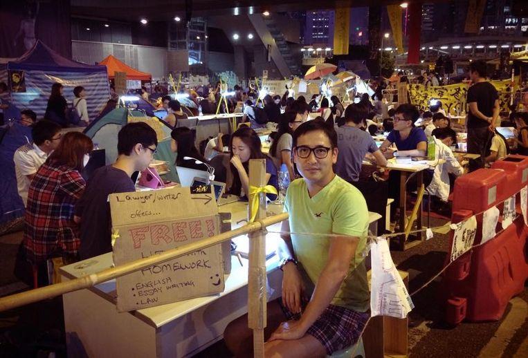 Jason Y. Ng op Connaught Road in Hongkong. Hij heeft er een kantoortje gebouwd waar hij 's avonds en in de weekenden lesgeeft in Engels, essayistiek en rechten. Beeld Foto: Jason Y. Ng