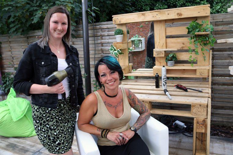 Cindy Van der Weehe (zittend) in haar buitenkapsalon met collega Shana Van Looy.