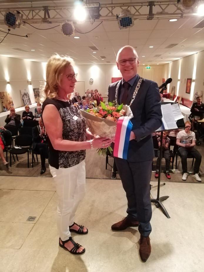 Burgemeester Carol van Eert overhandigt Jannie Luteijn-Roelofsen een bos bloemen kort na haar onderscheiding.