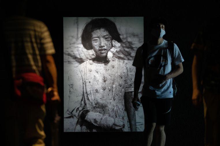 Bezoekers van het Hiroshima Peace Memorial Museum gisteren bij een foto van Yukiko Fujii (10) die de bom overleefde maar later stierf aan kanker op haar 42ste.  Beeld Getty Images
