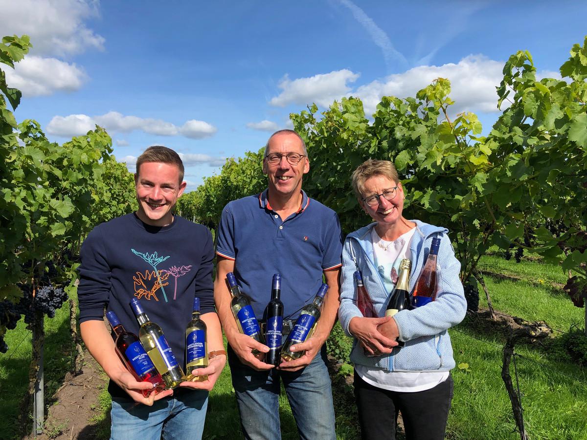 Bas, John en Wilma Huisman van De Reestlandhoeve met de prijsinnende wijnen van hun wijngoed in de wijngaard.