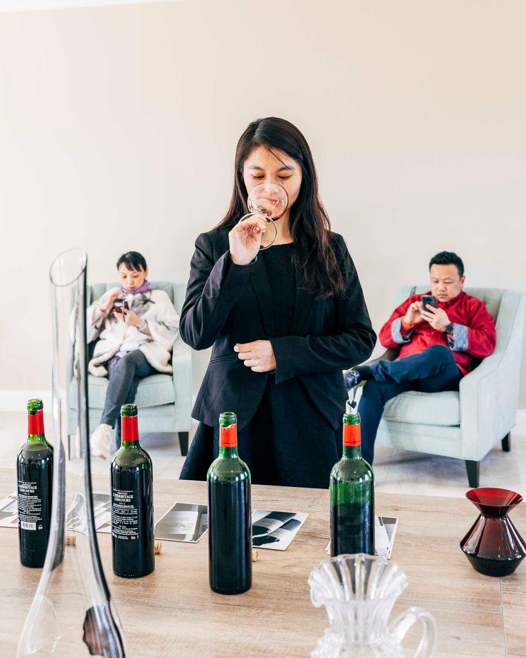Tijdens de week van de wijn in Bordeaux vliegen sommeliers speciaal over vanuit China om gasten te ontvangen in de hernieuwde chateaus. Een afgestudeerde sommelier proeft de verschillende wijnen, terwijl de investeerders in de achtergrond verveeld op hun mobiel kijken. Beeld Rebecca Fertinel