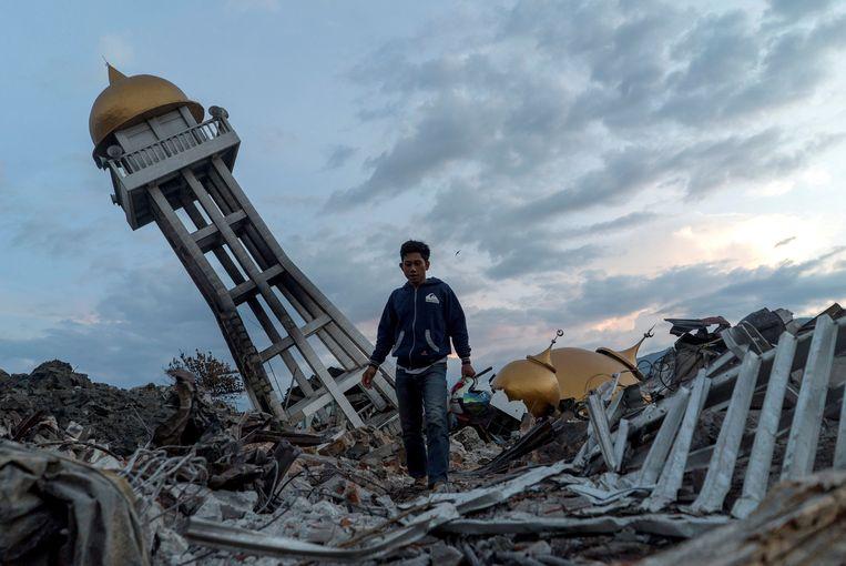 Een inwoner van Palu tussen het puin van de aardbeving en tsunami die vrijdag 28 september het Indonesische eiland Sulawesi trof. Beeld Reuters