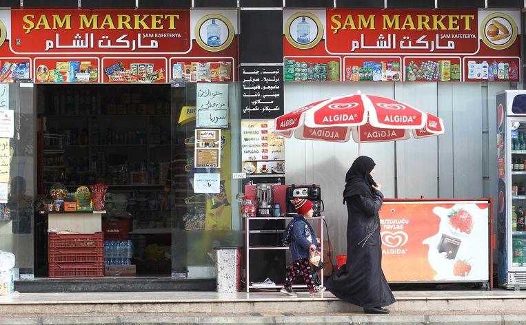 Een vrouw en een kind verlaten een Syrische winkel in de Turkse plaats Mersin. Beeld afp