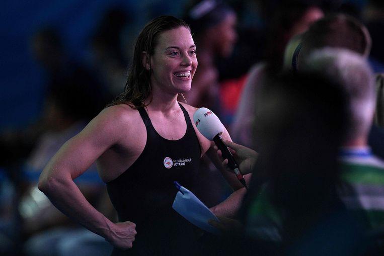 Na afloop van haar race op de 100 meter vrij staat Femke Heemskerk de Nederlandse pers te woord. Beeld AFP