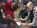 Kees Timmermans (L) en Marco Slockers (R) helpen Cas (rode overall) en Luuk (met bril) met de bouw van hun racewagen