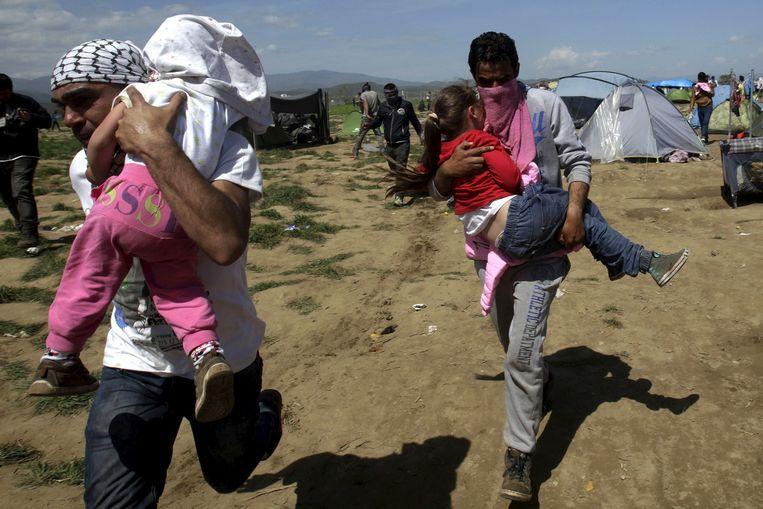 Migranten rennen weg met kinderen die in contact zijn gekomen met traangas. Beeld null
