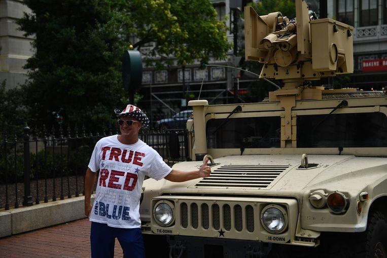 Een Trump-aanhanger voor een geparkeerde Humvee.