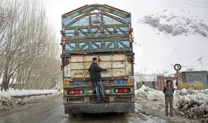 Een jongeman laat zich achter een vrachtwagen meevoeren naar Kabul, in Afghanistan. Foto Massoud Hossaini
