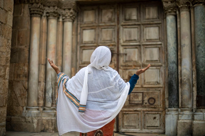 Een vrouw bidt voor de Kerk van het Heilig Graf in de oude stad van Jerusalem.
