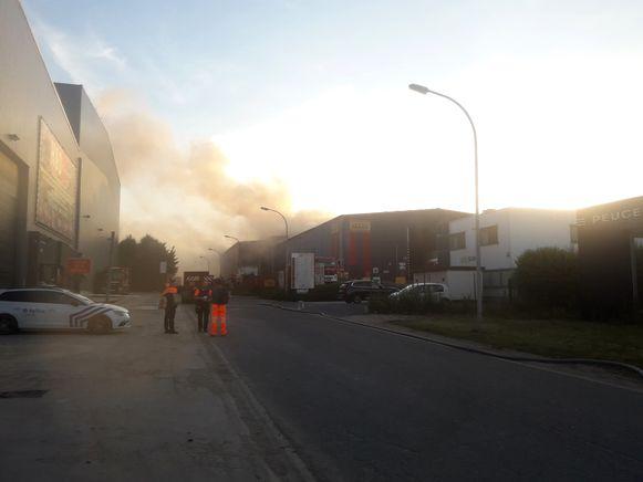 De brand bij Maes-Containers gaat gepaard met dikke, zwarte rook.