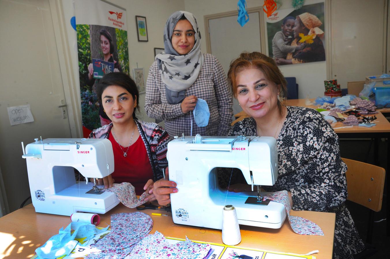 Ladan (links) en Farida achter de naaimachines en Zahraa met een mondkapje er achter.