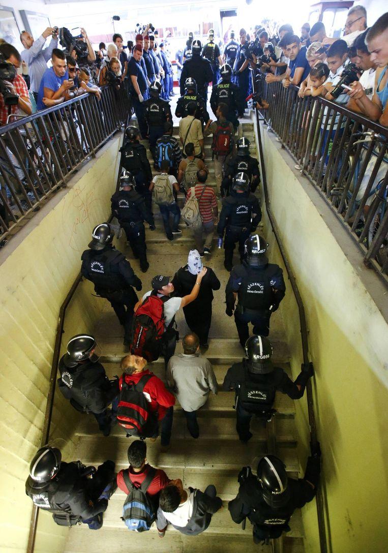 Migranten die de trein bij Bicske hebben verlaten, worden door de Hongaarse politie begeleid naar een registratiekamp. Eerst weigerden ze uit de trein te komen omdat ze door wilden reizen naar Duitsland.Ze zijn bang dat ze na registratie Hongarije niet meer kunnen verlaten. Beeld reuters