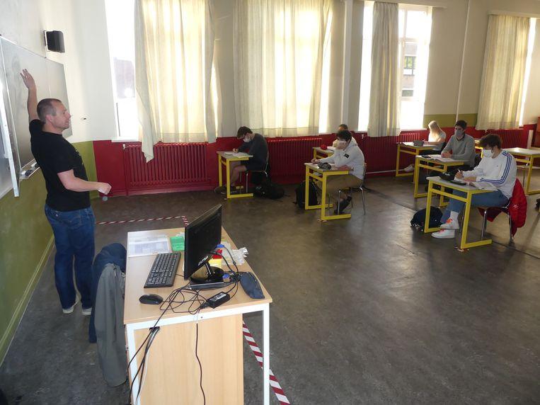 Wiskundeleraar Jan De Neve blijft in zijn afgebakende zone. De leerlingen zitten op de nodige afstand van elkaar, met mondmasker.