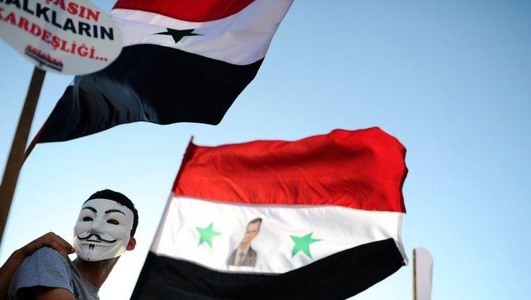Een aanhanger van Assad met de Syrische vlag. Beeld afp