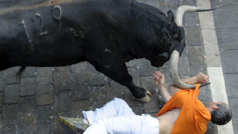 Een meerennende man wordt aan zijn t-shirt meegetrokken door een stier in Pamplona, in juli.