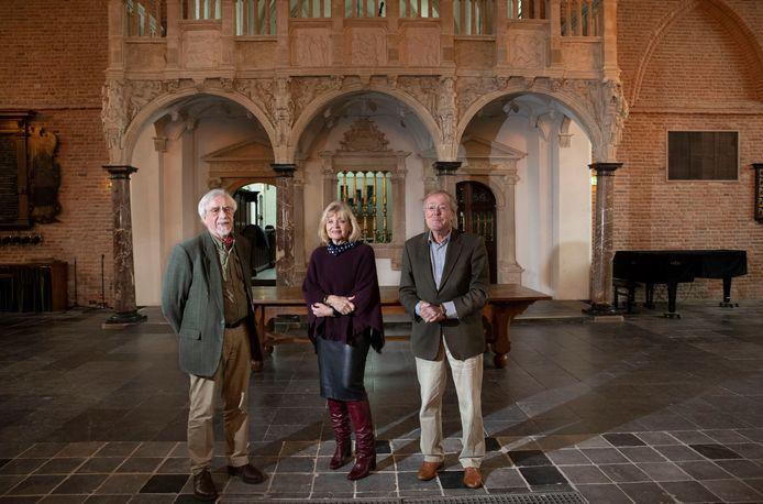 Kunsthistoricus Anton van Run (links) heeft een boek geschreven over het doksaal (op achtergrond) van de Cunerakerk, rechts bestuursleden van de Cunerakerk Maria van de Berg en Willem van Ommeren.