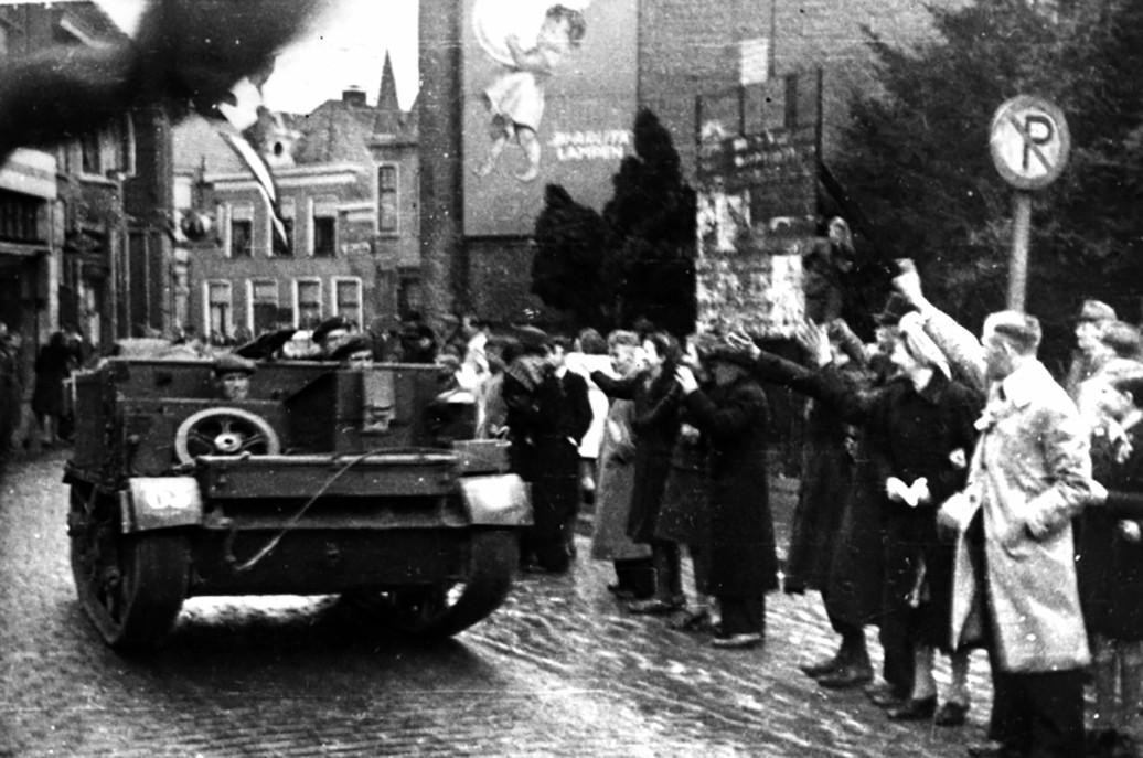 Oldenzalers zwaaien uitbundig naar hun bevrijders, die in legervoertuigen door de stad rijden.