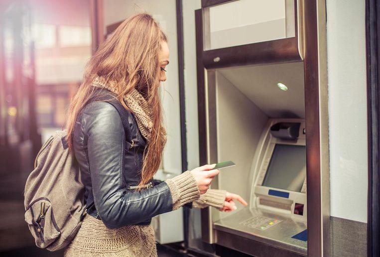 Een vrouw haalt in het buitenland geld af met haar kredietkaart.