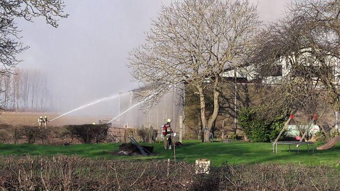 De brandweer gaat de brand in de landbouwschuur te lijf.