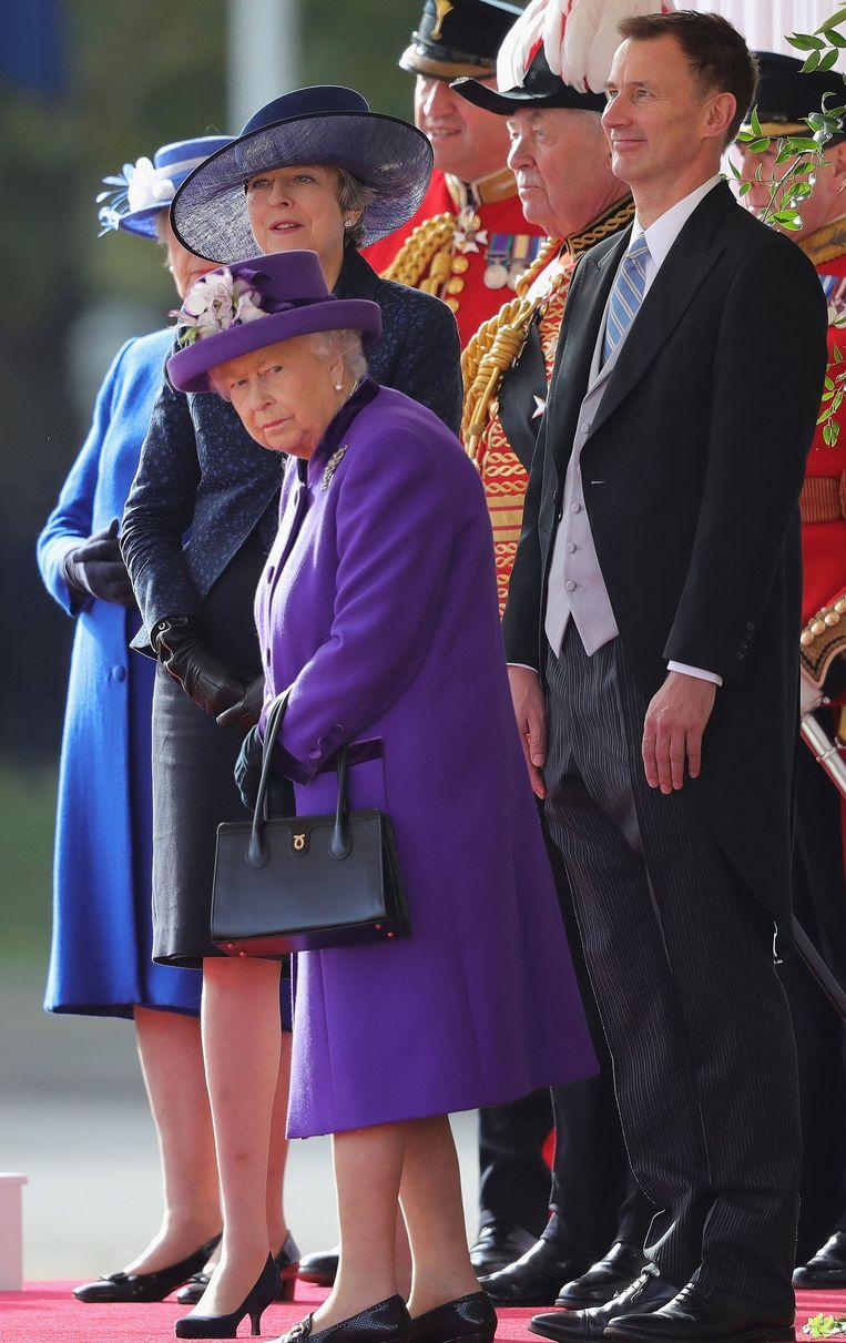Koningin Elizabeth II naast Jeremy Hunt, minister van buitenlandse zaken en Premier Theresa May.  Beeld AFP