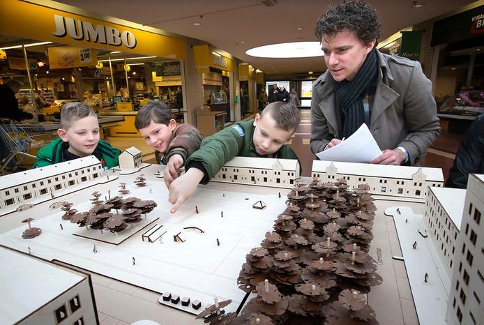 Dirk bekijkt met kinderen uit de buurt de maquette van het Nelson Mandelaplein. De maquette staat in het winkelcentrum om input voor het nieuwe plein te krijgen van de buurtbewoners. Foto: Joyce van Belkom/Pix4Profs