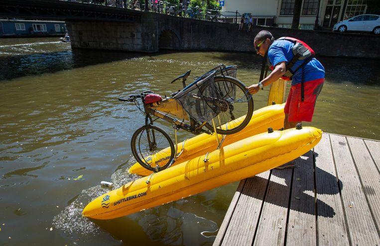 Dhruv Boruah laat zijn waterfiets in de gracht glijden. De milieuactivist uit Londen vist plastic uit het water. Beeld Dingena Mol