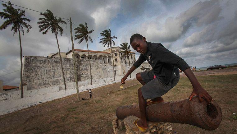 Een Ghanese jongen speelt met een koloniaal kanon voor het Nederlandse slavenfort Elmina in Ghana, een van de belangrijkste gevangenissen van de Transatlantische slavenhandel, waar van hun vrijheid beroofde Afrikanen onmenselijk wreed werden behandeld voor zij geketend naar Suriname, de Antillen en Amerika werden verscheept. Beeld epa