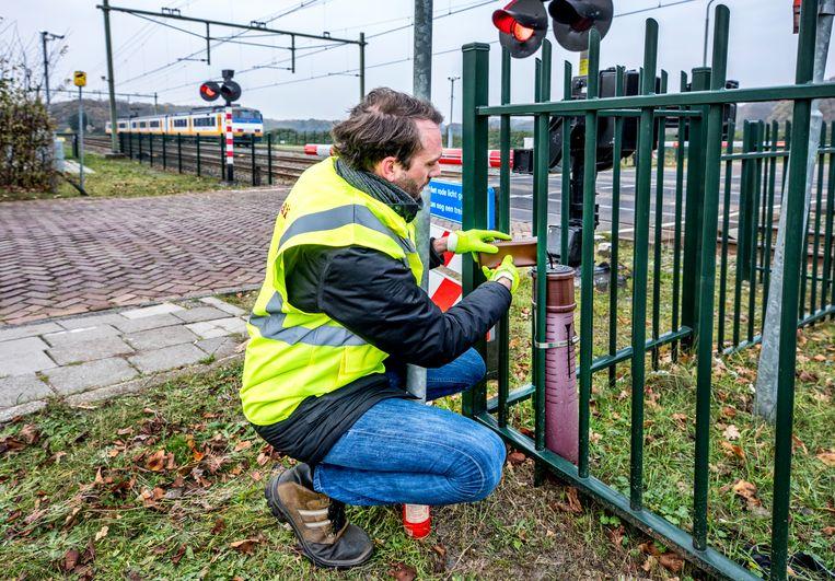 Jeff Diks van Prorail vult een geurzuiltje aan bij Santpoort-Noord. Beeld Raymond Rutting / de Volkskrant