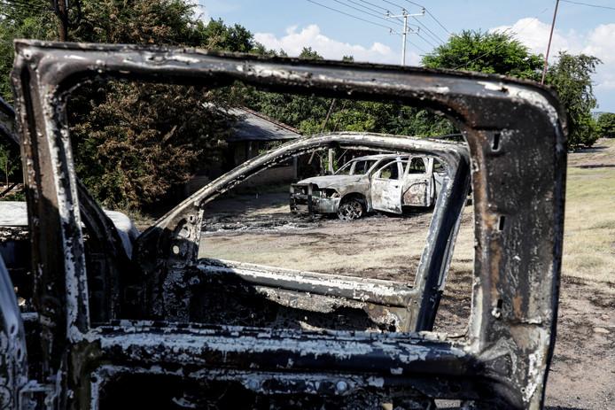 De uitgebrande politiewagens van de agenten die in een hinderlaag werden doodgeschoten.