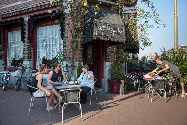 Terwijl Rob van Ginhoven de tafel dekt maakt Janna nog even een praatje met twee vaste klanten Beeld Dingena Mol