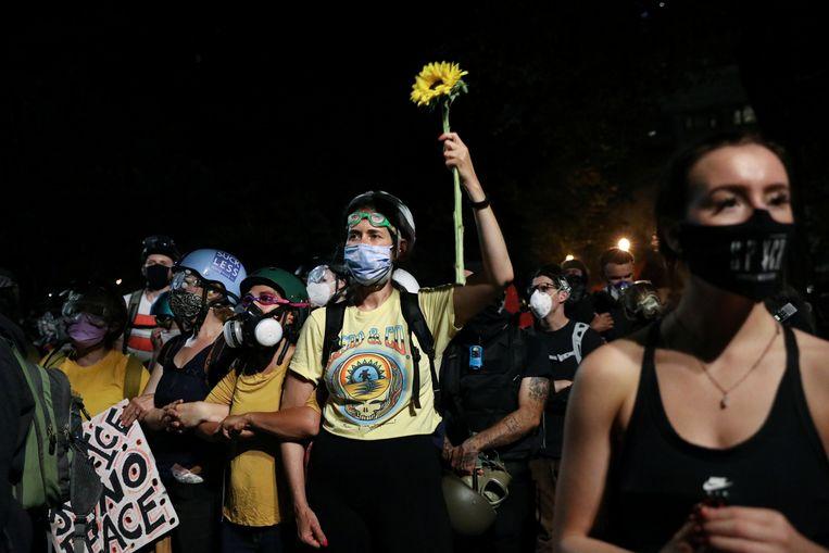 Vrouwen vormen een 'muur van moeders' tegenover de agenten van Trump. Beeld REUTERS