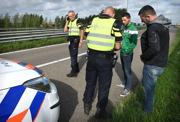 De politie controleert de papieren van de twee Albanezen en vragen waar ze heen gaan. De Albanezen proberen via Nederland naar Engeland te komen.  Beeld Marcel van den Bergh