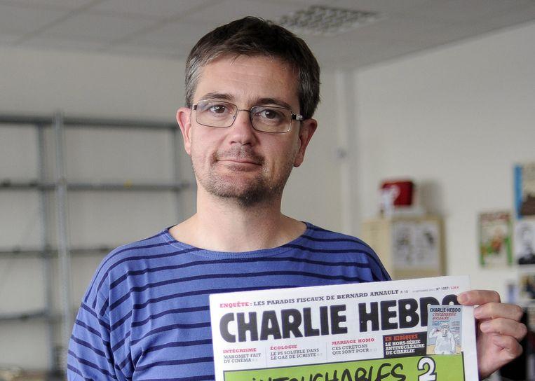 Hoofdredacteur Stéphane Charbonnier in 2012, met het exemplaar van de Charlie Hebdo met de gewraakte cartoons Beeld epa