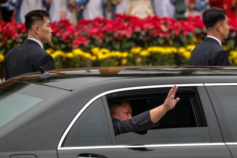 Kim zwaait vanuit zijn gepantserde limousine waarmee hij doorreist naar Hanoi.