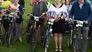 In oude klederdracht de fiets op