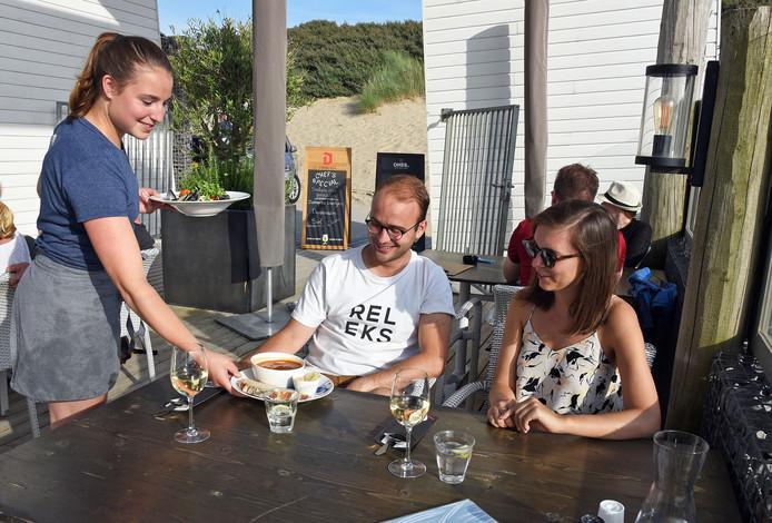 Gastvrouw Anouk serveert bij strandpaviljoen Ruig in Cadzand-Bad. Vooral in de horeca zijn 's zomers veel handen nodig. Dat heeft invloed op het aantal WW-uitkeringen in deze sector.