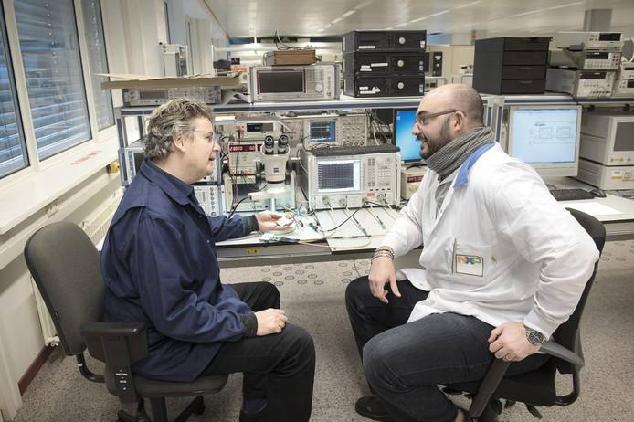 """Systeemarchitect Marcel Geurts (links) in gesprek met onderzoeker Marco Piacentini in het laboratorium van NXP. """"Wij maken bij NXP wel ongeveer 2,5 miljard kleine antenneversterkertjes per jaar."""" foto Bert Beelen"""