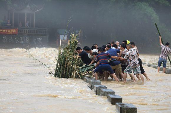 Mannen proberen aangespoelde bamboe te verwijderen van een brug in Liuzhou.